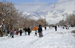 People walk on a snow-covered road in Quetta, capital of Pakistan's southwestern Baluchistan province, Monday, Jan. 13, 2020. Severe winter weather has struck parts of Afghanistan and Pakistan, with heavy snowfall, rains and flash floods that left more than 40 dead, officials said Monday as authorities struggled to clear and reopen highways and evacuate people to safer places. (AP Photo/Arshad Butt)