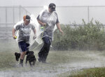 Kelly Buckle, right, of Brielle, N.J., and her ten-year-old son Evan, run with their new puppy Taz through a park in Manasquan, N.J., during a driving rain from Tropical Storm Fay, Friday, July 10, 2020. Fast-moving Tropical Storm Fay made landfall in New Jersey, Friday amid heavy, lashing rain that closed beaches and flooded shore town streets. (Thomas P. Costello/The Asbury Park Press via AP)