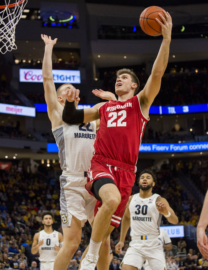 FILE - In this Dec. 8, 2018, file photo, Wisconsin forward Ethan Happ, right, goes up for a basket against Marquette forward Joey Hauser, left, during the second half of an NCAA college basketball game, in Milwaukee. Wisconsin hosts Purdue on Friday night, Jan. 11, 2019, in a matchup between two of the top players in the Big Ten _ Ethan Happ and Carsen Edwards.(AP Photo/Darren Hauck, File)