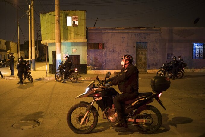 Police enforce the curfew declared by the government due to the new coronavirus pandemic, in El Callao, on the outskirts of Lima, Peru, Wednesday, April 8, 2020. (AP Photo/Rodrigo Abd).