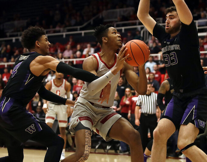 Stanford's KZ Okpala, center, looks to shoot between Washington's Sam Timmins (33) and Matisse Thybulle, left, in the first half of an NCAA college basketball game Sunday, March 3, 2019, in Stanford, Calif. (AP Photo/Ben Margot)