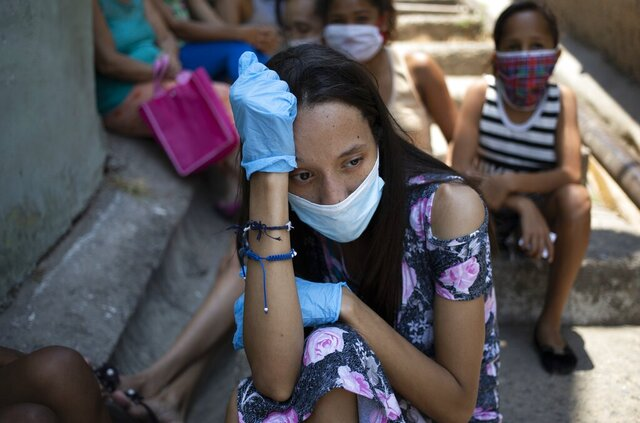 A woman wearing a mask and gloves against the spread of the new coronavirus, waits outside a soup kitchen run by nuns, waiting for it to open and get some food, in Caracas' Petare slum in Venezuela, Thursday, April 30, 2020. To avoid the spread of the new coronavirus the soup kitchen is giving out the food to take home. (AP Photo/Ariana Cubillos)