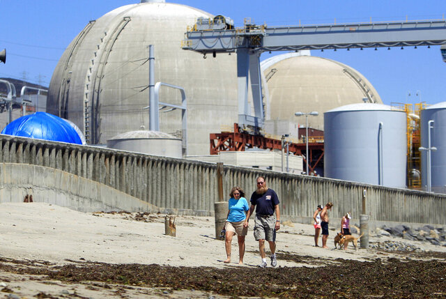 FILE - In this June 30, 2011 file photo, people walk on the sand near the shuttered San Onofre Nuclear Generating Station in San Clemente, Calif. Dismantling of the shuttered power plant on the Southern California coast will begin in February 2020. (AP Photo/Lenny Ignelzi, File)