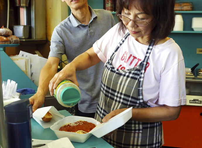 In this Thursday, March 14, 2019 photo, Belinda Lau, manager of the Wiki Wiki Drive Inn takeout restaurant in Honolulu, sprinkles cheese on an order of spaghetti in a styrofoam container. Hawaii would be the first state in the U.S. to ban most plastics used at restaurants under legislation that aims to cut down on waste that pollutes the ocean. Dozens of cities across the country have banned plastic foam containers, but Hawaii would be the first to bar them statewide. (AP Photo/Audrey McAvoy)