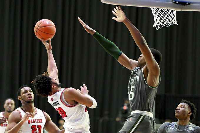 Western Kentucky guard Dayvion McKnight (20) tries to shoot over UAB center Trey Jemison (55) in the first half of an NCAA college basketball game in the Conference USA men's tournament, in Frisco, Texas, Friday, March 12, 2021. (AP Photo/Matt Strasen)