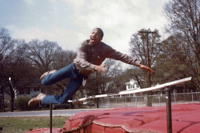 In this late 1980's photo provided by musician DJ Nabs, his childhood friend, Alton Lucas, jumps in a field at Durham High School in Durham, N.C. As a teenager, Alton Lucas believed basketball or music would pluck him out of North Carolina and take him around the world. (Courtesy DJ Nabs via AP)
