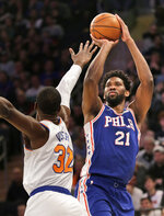 Philadelphia 76ers' Joel Embiid, right, shoots over New York Knicks' Noah Vonleh during the first half of an NBA basketball game, Sunday, Jan. 13, 2019, in New York. (AP Photo/Seth Wenig)
