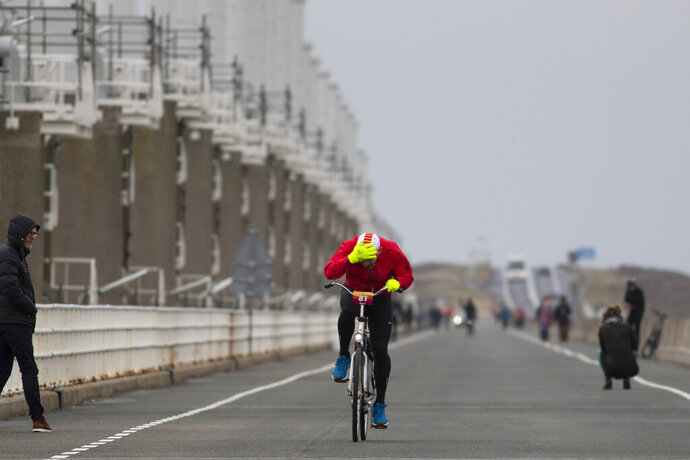 A competitor holds onto his cap as he battles gale force winds during the Dutch Headwind Cycling Championships on the storm barrier Oosterscheldekering near Neeltje Jans, south-western Netherlands, Sunday, Feb. 9, 2020. (AP Photo/Peter Dejong)