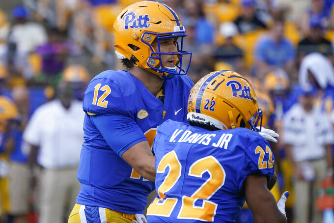 Pittsburgh quarterback Nick Patti (12) hands off to running back Vincent Davis (22) during the first half of an NCAA college football game, Saturday, Sept. 18, 2021, in Pittsburgh. (AP Photo/Keith Srakocic)