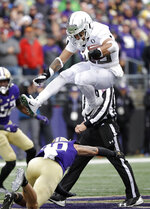 Oregon's Cyrus Habibi-Likio leaps to avoid a tackle by Washington's Asa Turner in the second half of an NCAA college football game Saturday, Oct. 19, 2019, in Seattle. Oregon won 35-31. (AP Photo/Elaine Thompson)