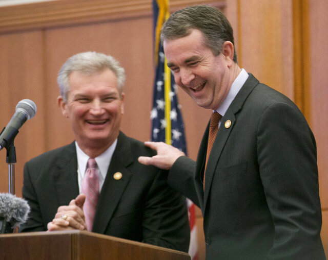 FILE - In this Wednesday March 21, 2018 file photo, Virginia Gov. Ralph Northam, right, with Sec. of Finance, Aubrey Lane, as he makes remarks at the Capitol in Richmond, Va. Proposed pay boosts for Virginia teachers and state workers are in serious jeopardy as state officials scramble to figure out just how bad the conoravirus' impact will be on the state budget (AP Photo/Steve Helber)