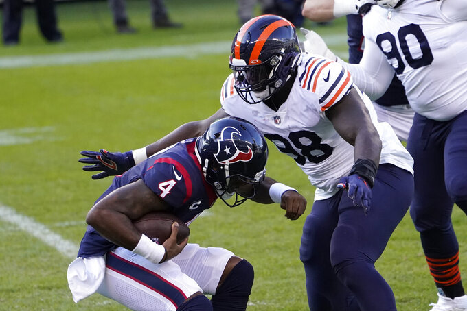Chicago Bears' Bilal Nichols (98) sacks Houston Texans quarterback Deshaun Watson (4) during the first half of an NFL football game, Sunday, Dec. 13, 2020, in Chicago. (AP Photo/Charles Rex Arbogast)