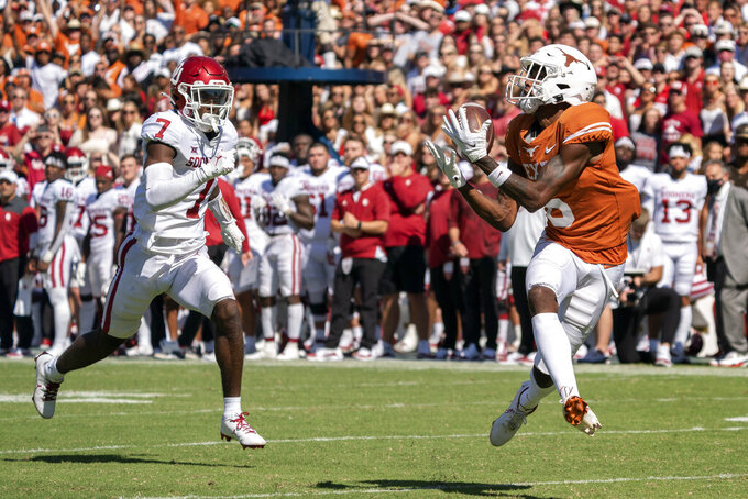 Texas wide receiver Joshua Moore (6) hauls in a touchdown pass in front of Oklahoma cornerback Latrell McCutchin (7) during the first half of an NCAA college football game at the Cotton Bowl, Saturday, Oct. 9, 2021, in Dallas. (AP Photo/Jeffrey McWhorter)
