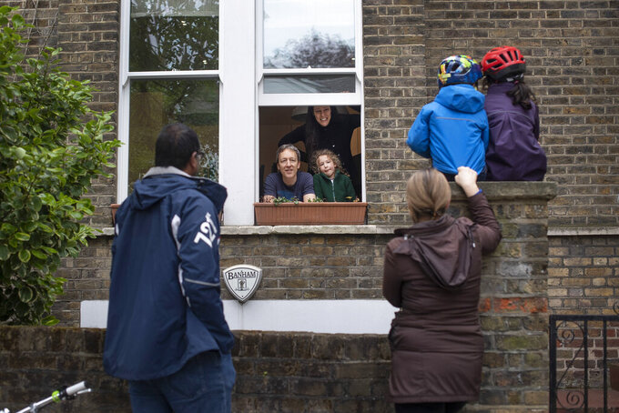 Two families who gave permission to be photographed, maintain social distancing while talking to each other outside a home in Hampstead, north London, Sunday May 3, 2020, as the UK continues in lockdown to help curb the spread of the coronavirus. The highly contagious COVID-19 coronavirus has impacted on nations around the globe, many imposing self isolation and exercising social distancing when people move from their homes. (Victoria Jones / PA via AP)