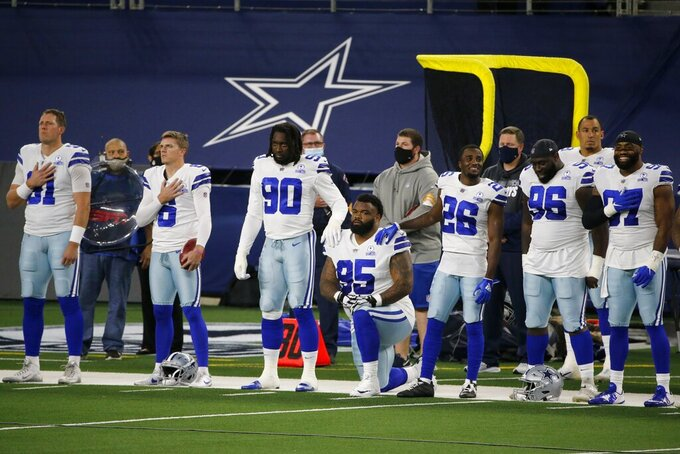 The Dallas Cowboys line the sideline during the playing of the national anthem before the first half of an NFL football game against the Arizona Cardinals in Arlington, Texas, Monday, Oct. 19, 2020. (AP Photo/Michael Ainsworth)