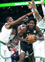 Brooklyn Nets forward Ed Davis, center right, is pressured by Boston Celtics guard Kyrie Irving, left, guard Jaylen Brown, rear, and forward Daniel Theis (27) on a drive to the basket during the first quarter of an NBA basketball game in Boston, Monday, Jan. 7, 2019. (AP Photo/Charles Krupa)