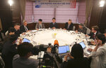 In this Wednesday, June 26, 2019, photo, South Korean Unification Minister Kim Yeon-chul, top center, speaks during a group interview at a hotel in Seoul, South Korea. The U.S. and North Korea both feel the need to resume diplomacy and are trying to narrow their differences for new summit talks, Kim said as he contrasted their efforts with the tensions surrounding Iran's collapsing nuclear accord. The sign at top reads: