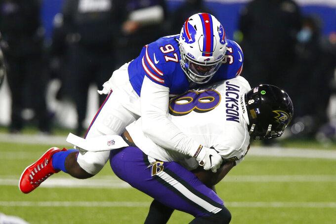 Buffalo Bills defensive end Mario Addison (97) sacks Baltimore Ravens' Lamar Jackson (8) during the first half of an NFL divisional round football game Saturday, Jan. 16, 2021, in Orchard Park, N.Y. (AP Photo/John Munson)