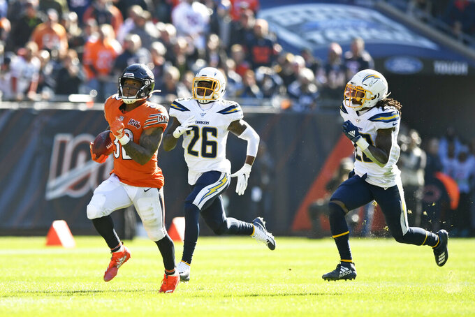 Chicago Bears running back David Montgomery (32) runs from Los Angeles Chargers defenders Casey Hayward (26) and Rayshawn Jenkins, right, during the first half of an NFL football game, Sunday, Oct. 27, 2019, in Chicago. (AP Photo/Paul Beaty)