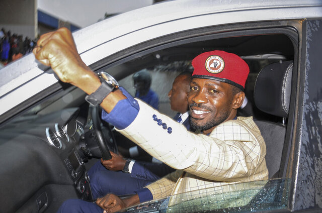 FILE—In this file photo of Thursday Jan.9, 2020, Ugandan presidential hopeful and political activist Bobi Wine, whose real name is Kyagulanyi Ssentamu, raises his fist in the air to gathered supporters as he leaves after meeting with the Electoral Commission, in Kampala, Uganda.  A bodyguard for Ugandan opposition leader Bobi Wine was killed and two journalists injured on Sunday, Dec. 27,  amid violent confrontations between security forces and followers of the singer and lawmaker who is challenging the country's long-time leader. A tearful Wine, whose real name is Kyagulanyi Ssentamu, said his bodyguard had died of his injuries after allegedly being run over by a truck belonging to the military police.  (AP Photo/Ronald Kabuubi-File)