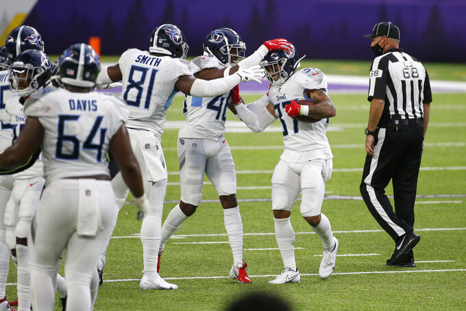 Tennessee Titans safety Amani Hooker, right, celebrates with teammates after intercepting a pass during the second half of an NFL football game against the Minnesota Vikings, Sunday, Sept. 27, 2020, in Minneapolis. The Titans won 31-30. (AP Photo/Bruce Kluckhohn)