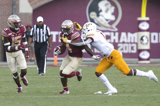 Florida State's Khalan Laborn, center, picks up yardage as Louisiana-Monroe's Tyler Glass makes the tackle in the third quarter of an NCAA college football game Saturday, Sept. 7, 2019, in Tallahassee Fla. (AP Photo/Steve Cannon)