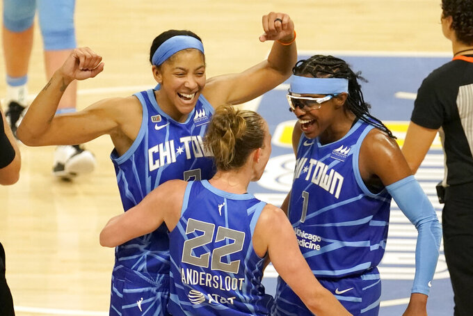Chicago Sky's Candace Parker, left, and Diamond DeShields (1) celebrate with Courtney Vandersloot after Vandersloot was fouled and scored in the act of shooting during the second half of a WNBA basketball game against the Connecticut Sun Thursday, June 17, 2021, in Chicago. The Sky won 81-75. (AP Photo/Charles Rex Arbogast)
