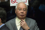 Former Malaysian Prime Minister Najib Razak adjusts his tie as he arrives at Kuala Lumpur High Court in Kuala Lumpur, Malaysia, Monday, April 29, 2019. Najib, his former deputy and several high-ranking former officials have already been charged with corruption after the election ushered in the first change of power since Malaysia's independence from Britain in 1957. (AP Photo/Vincent Thian)