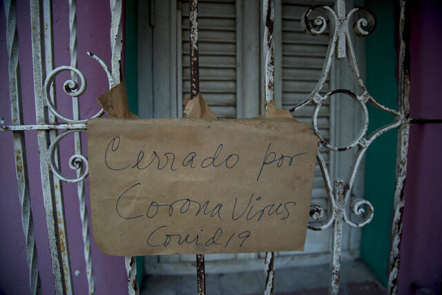 """The Spanish message """"Closed because of coronavirus COVID-19 hangs on the door of a business in Havana, Cuba, Friday, April 24, 2020. (AP Photo/Ismael Francisco)"""