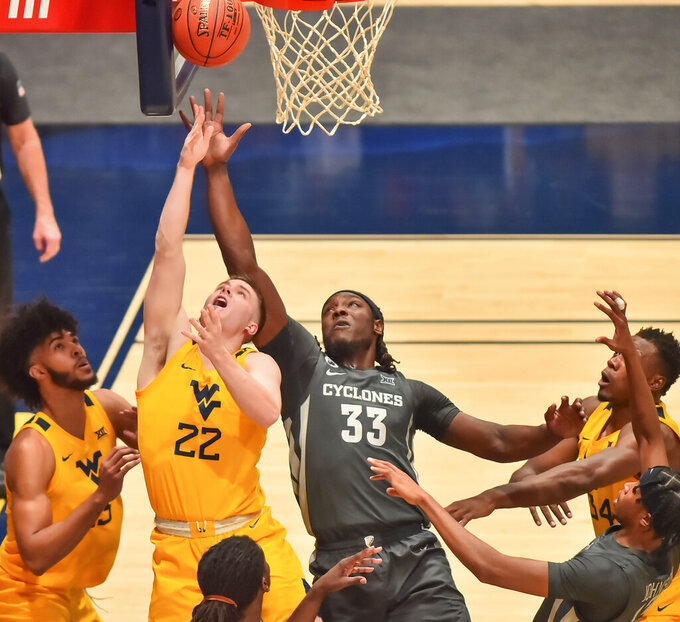 West Virginia guard Sean McNeil (22) shoots over Iowa State forward Solomon Young (33) during the first half of an NCAA college basketball game in Morgantown, W.V., Friday, Dec. 18, 2020. (William Wotring/The Dominion-Post via AP)