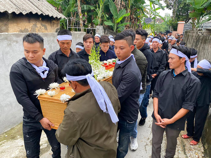 Relatives carry the coffin of Hoang Van Tiep to the church for a funeral ceremony Thursday, Nov. 28, 2019 in Dien Chau, Vietnam. The 18-year old Tiep was among the 39 Vietnamese who died when human traffickers carried them by truck to England in October, and whose remains were among the 16 repatriated to their homeland Wednesday. (AP Photo/Hau Dinh)