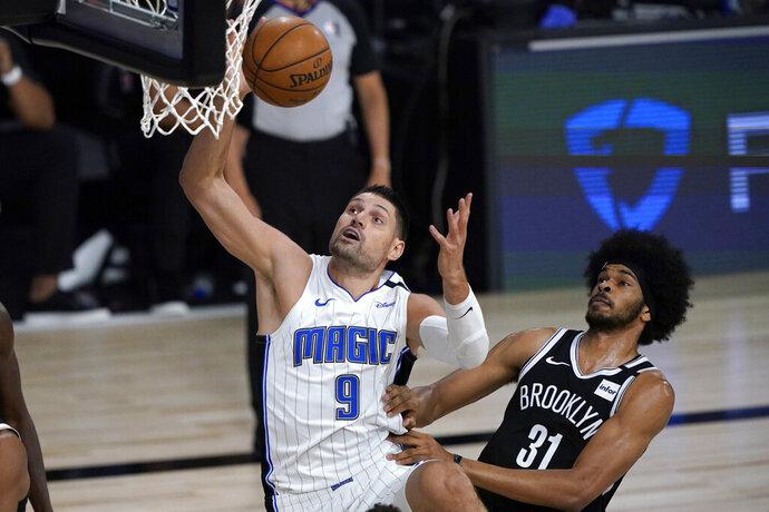 Orlando Magic's Nikola Vucevic (9) heads to the basket as Brooklyn Nets' Jarrett Allen (31) defends during the first half of an NBA basketball game Friday, July 31, 2020, in Lake Buena Vista, Fla. (AP Photo/Ashley Landis, Pool)