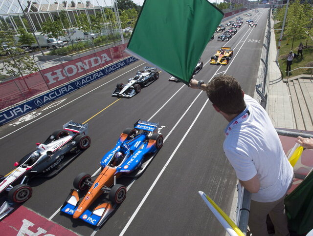 FILE - In this July 15, 2018, file photo, Jason Priestley waves the green flag to start an IndyCar auto race in Toronto. The stars of IndyCar were in Florida preparing to start their season when the coronavirus pandemic slammed the brakes on those plans 48 hours before the green flag.  Almost three months later, the series is finally set to go racing.  The 2020 season will open Saturday night, June 6, 2020, at Texas Motor Speedway in NBC's first ever primetime IndyCar race. (Frank Gunn/The Canadian Press via AP, File)