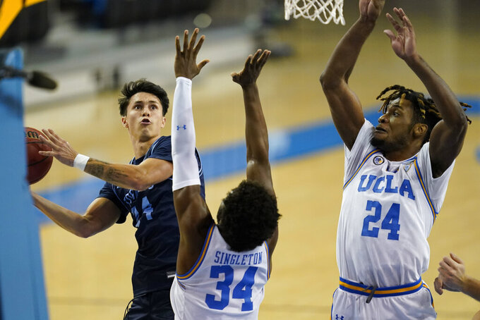 San Diego guard Chris Herren Jr., left, is defended by UCLA guard David Singleton (34) and forward Jalen Hill (24) during the first half of an NCAA college basketball game Wednesday, Dec. 9, 2020, in Los Angeles. (AP Photo/Ashley Landis)