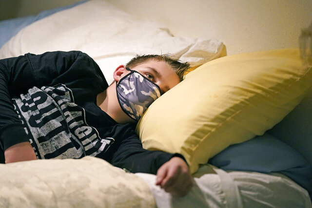 Cooper Wuthrich rests as he lays on a bed at the truck stop his family partly owns Tuesday, Dec. 15, 2020, in Montpelier, Idaho. Shortly after Thanksgiving, Wuthrich, 12, became one of hundreds of children in the U.S. diagnosed with a rare COVID-19 complication that landed him in an emergency room three hours away from his tiny hometown in a secluded Idaho valley. The boy's parents say he nearly died and their terrifying experience shows why people should wear masks in a conservative state where pushback can be fierce. (AP Photo/Rick Bowmer)