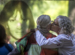"Photographed through a glass window that features a photograph, ESMA museum director Alejandra Naftal, right, kisses torture victim Ana Testa during the inauguration of an exhibit that recounts harrowing stories of dictatorship-era gender-based violence, at the former Naval Mechanics School, ESMA, once the era's biggest clandestine detention and torture center, now the Buenos Aires ESMA museum and memorial, in Buenos Aires, Argentina, Thursday, March 14, 2019.  Naftal said that since the former secret prison re-opened as a museum in 2015, ""women and young people began telling us that we had forgotten about the gender perspective when recounting the acts that happened here. (AP Photo/Daniel Jayo)"