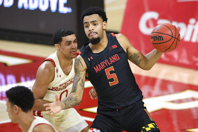 Maryland guard Eric Ayala (5) handles the ball in front of Wisconsin guard D'Mitrik Trice (0) during the first half of an NCAA college basketball game Wednesday, Jan. 27, 2021, in College Park, Md. (AP Photo/Nick Wass)