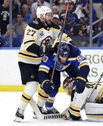 St. Louis Blues center Ryan O'Reilly (90) falls between Boston Bruins defenseman John Moore (27) and goaltender Tuukka Rask (40), of Finland, during the second period of Game 6 of the NHL hockey Stanley Cup Final Sunday, June 9, 2019, in St. Louis. (AP Photo/Jeff Roberson)