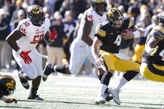 Iowa quarterback Nate Stanley (4) scrambles from Maryland linebacker Mbi Tanyi (50) during the first half of an NCAA college football game, Saturday, Oct. 20, 2018, in Iowa City, Iowa. (AP Photo/Charlie Neibergall)