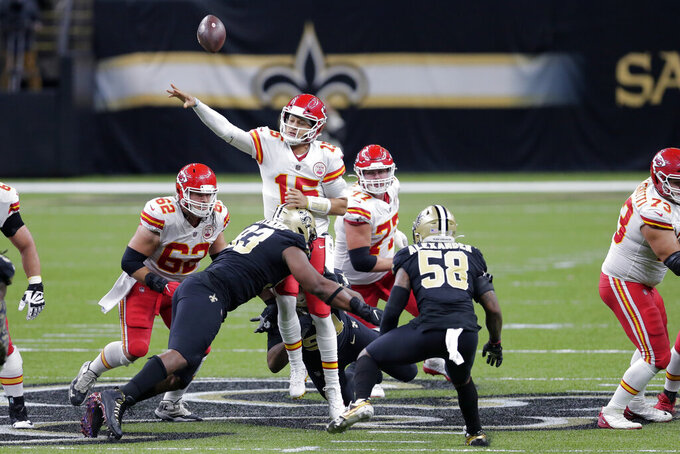 Kansas City Chiefs quarterback Patrick Mahomes (15) is hit by New Orleans Saints defensive tackle David Onyemata (93) as he passes in the first half of an NFL football game in New Orleans, Sunday, Dec. 20, 2020. (AP Photo/Brett Duke)