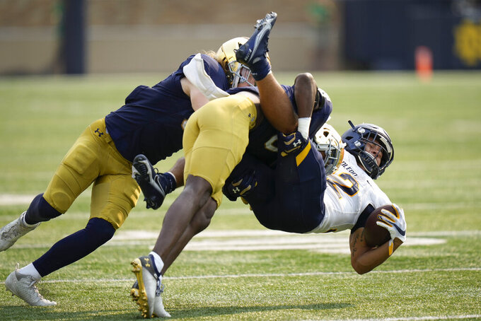 Toledo running back Bryant Koback (22) gets tackled by Notre Dame defenders in the second half of an NCAA college football game in South Bend, Ind., Saturday, Sept. 11, 2021. Notre Dame won 32-29. (AP Photo/AJ Mast)
