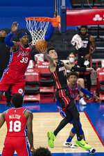 Miami Heat's Tyler Herro, center, puts up the shot with Philadelphia 76ers' Matisse Thybulle, right, and Dwight Howard, left, defending during the first half of an NBA basketball game, Thursday, Jan. 14, 2021, in Philadelphia. (AP Photo/Chris Szagola)