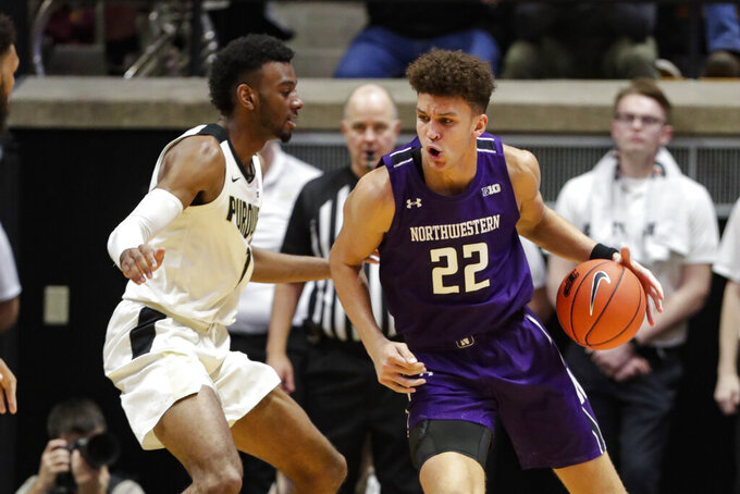 Northwestern forward Pete Nance (22) drives on Purdue forward Aaron Wheeler (1) during the second half of an NCAA college basketball game in West Lafayette, Ind., Sunday, Dec. 8, 2019. Purdue defeated Northwestern 58-44. (AP Photo/Michael Conroy)