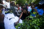 Relatives attend a burial service for four people killed in the past weeks' protest, in Port-au-Prince, Haiti, Tuesday, Nov. 19, 2019. More than 40 people have been killed and dozens injured in more than two months of demonstrations organized by opposition leaders demanding the resignation of President Jovenel Moise amid anger over corruption, ballooning inflation and a scarcity of basic goods. (AP Photo/Dieu Nalio Chery)