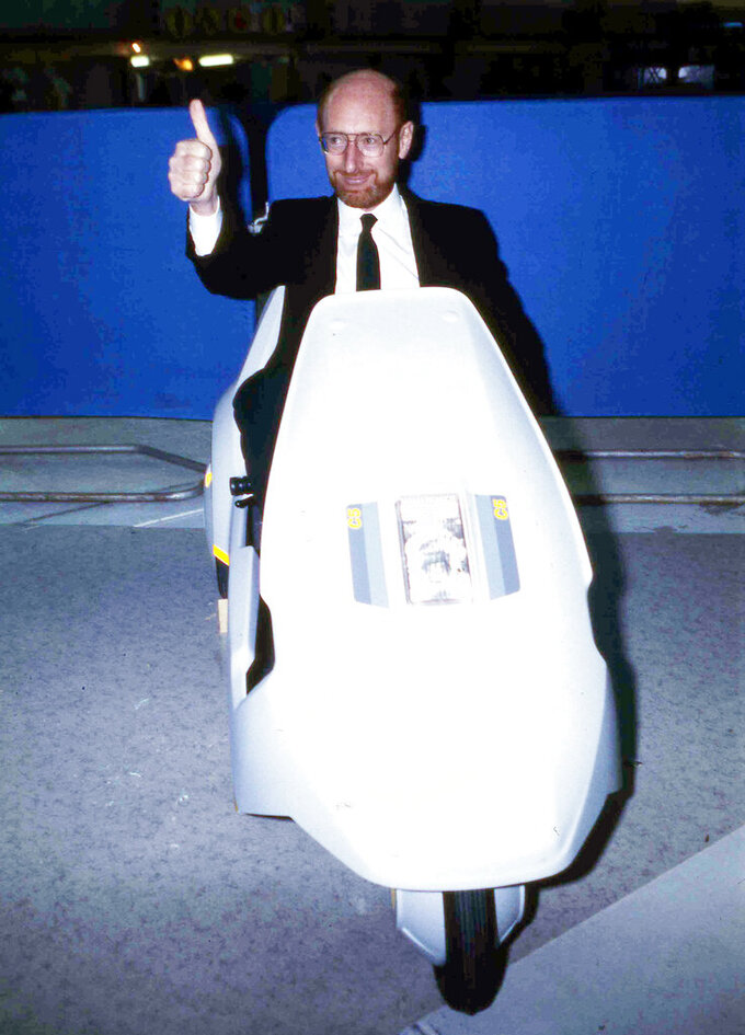 FILE - In this Jan. 10, 1985 file photo, British industrialist Sir Clive Sinclair, pictured at the controls of his newly-launched Sinclair C5 battery operated personal transport, in London, England. Sinclair, the British inventor and entrepreneur who arguably did more than anyone else to inspire a generation of children into a life-long passion for computers and gaming, has died. He was 81. Sinclair, who rose to prominence in the early 1980s with a series of affordable home computers that offered millions their first glimpse into the world of coding as well as the adrenaline rush of playing games on screens, died on Thursday, Sept. 17, 2021 morning after a long illness with cancer. (AP Photo/Bob Dear, File)