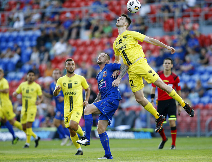 Liam McGing, right, of Wellington Phoenix jumps over Roy O'Donovan of the Newcastle Jets to head the ball during their A-League match in Newcastle on Feb. 28, 2021. The A-League announced Friday, April 30, 2021, that the Phoenix, fighting for a playoff spot, will play a home match in the New Zealand capital of Wellington on May 22. (Darren Pateman/AAP Image via AP)