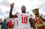 Houston Cougars defensive tackle Ed Oliver does the Cougar Paw with his teammates and the Bayou Bucket trophy after defeating Rice in a NCAA college football game Saturday, Sept. 1, 2018, in Houston. (AP Photo/Michael Wyke)