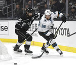 San Jose Sharks right wing Kevin Labanc (62) and Los Angeles Kings defenseman Drew Doughty (8) chase the puck behind the net during the first period of an NHL hockey game, Monday, Nov. 25, 2019, in Los Angeles. (AP Photo/Michael Owen Baker)