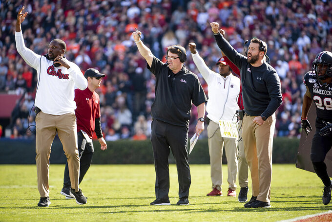 South Carolina head coach Will Muschamp, center, John Scott, left, and Coleman Hutzler, signal to players during the first half of an NCAA college football game against Clemson, Saturday, Nov. 30, 2019, in Columbia, S.C. (AP Photo/Sean Rayford)