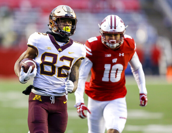 Minnesota wide receiver Demetrius Douglas out runs Wisconsin safety Seth Currens on a punt return for a touchdown during the first half of an NCAA college football game Saturday, Nov. 24, 2018, in Madison, Wis. (AP Photo/Andy Manis)